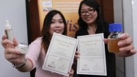 The two young researchers show off their awards